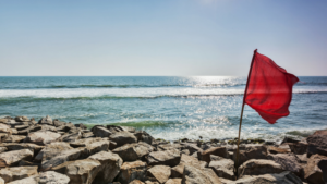 Red flag on a rocky beach